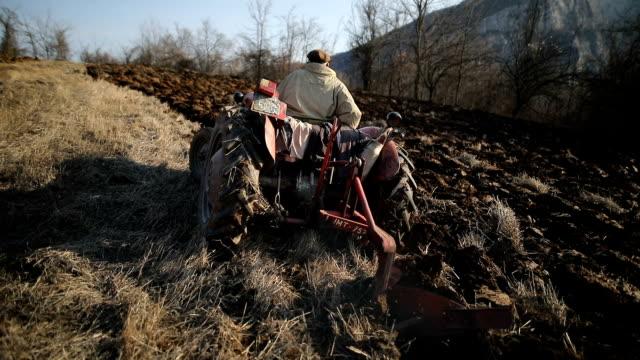 vídeos y material grabado en eventos de stock de hombre mayor que conduce el pequeño tractor y la actividad de arado field. agricultural. escena no urbana - grano planta
