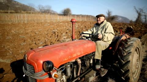 stockvideo's en b-roll-footage met senior man rijden kleine trekker en ploegen veld. landbouwactiviteit. niet-stedelijke scene - tractor