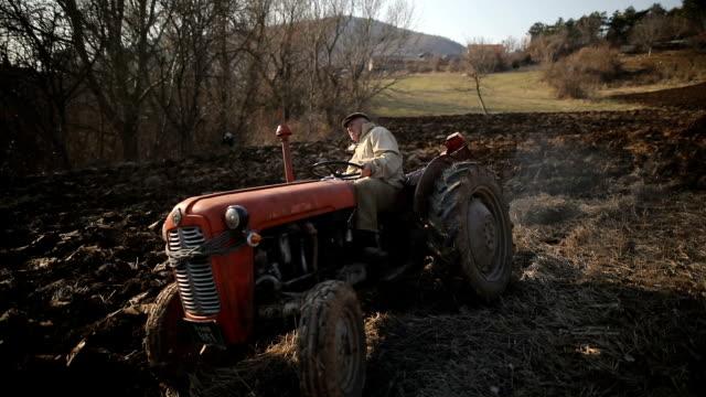 stockvideo's en b-roll-footage met senior man rijden kleine trekker en ploegen veld. landbouwactiviteit. niet-stedelijke scene - cereal plant