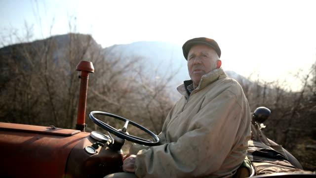 vídeos y material grabado en eventos de stock de hombre mayor conduciendo tractor pequeño y la actividad de arado field. agricultural - grano planta
