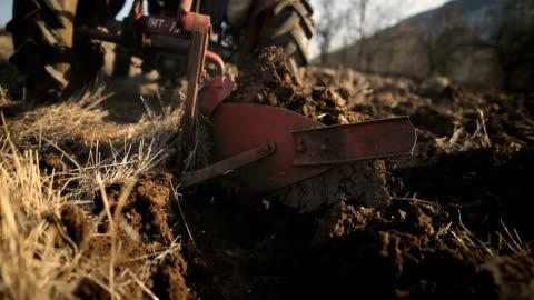 vídeos y material grabado en eventos de stock de hombre mayor conduciendo tractor pequeño y la actividad de arado field. agricultural - campo arado