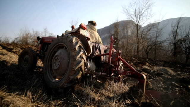 senior man driving small tractor and plowing field.agricultural activity - tractor stock videos & royalty-free footage