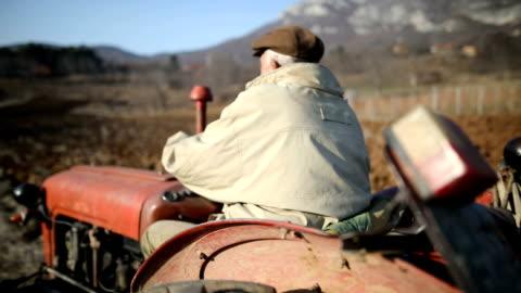 vídeos y material grabado en eventos de stock de senior man driving tractor pequeño y arar campo. actividad agrícola - arar