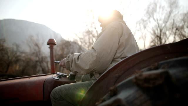 vídeos y material grabado en eventos de stock de senior man driving tractor pequeño y arar campo. actividad agrícola - campesino