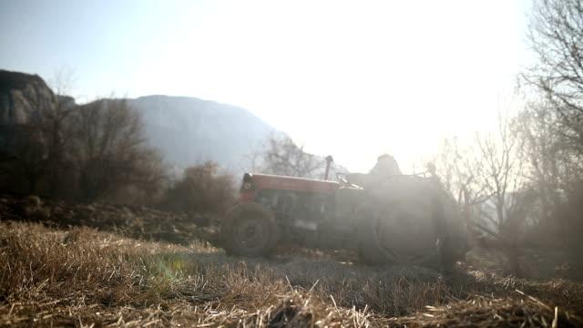 vídeos y material grabado en eventos de stock de hombre mayor que conduce el pequeño tractor y la actividad de arado field. agricultural, contaminación, humo - grano planta