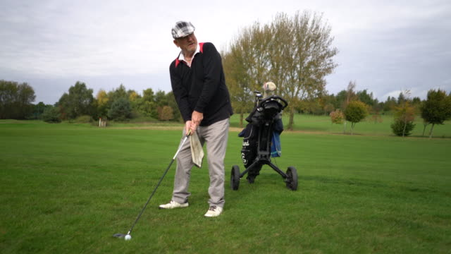 A senior man driving the ball from the fairway