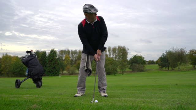 A senior man driving the ball from the fairway.