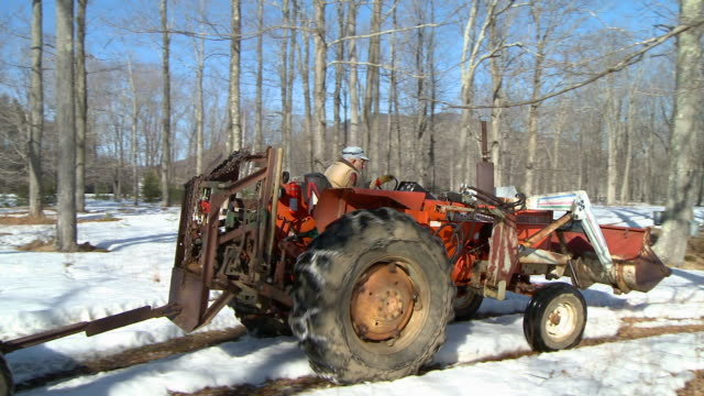 WS CS Senior man driving tractor in forest with tubing system, North Conway, New Hampshire, USA