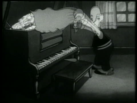 b/w 1937 animation senior man dumping bag of laundry into player piano / folded laundry emerging - 1937 stock-videos und b-roll-filmmaterial