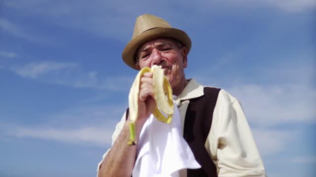 ms senior man eating banana / jacksonville beach, florida, usa  - napkin stock videos & royalty-free footage