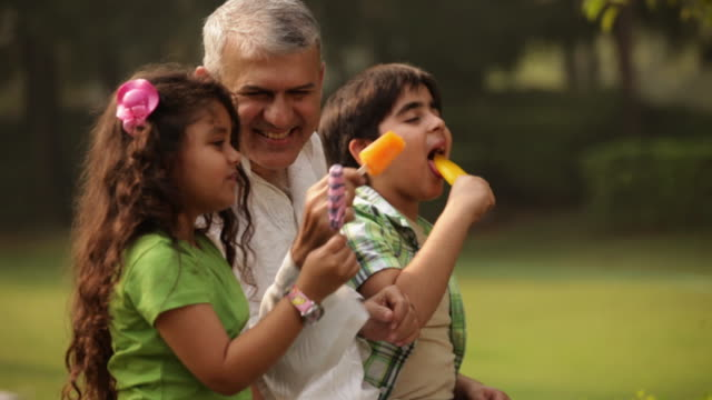 senior man eating ice cream with his grandchildren in a park  - dessert stock videos & royalty-free footage