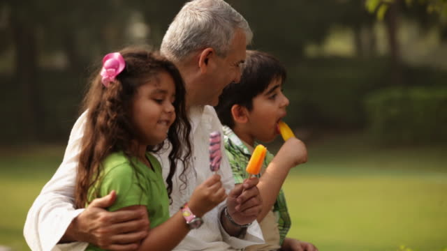 senior man eating ice cream with his grandchildren in a park  - wrist watch stock videos & royalty-free footage