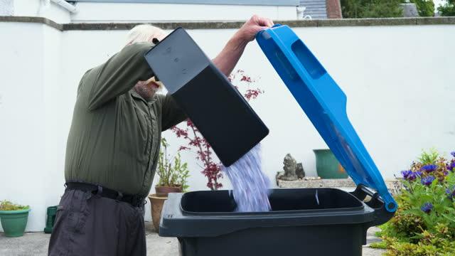 vídeos de stock, filmes e b-roll de idoso esvaziando papel picado em uma lixeira - plano americano