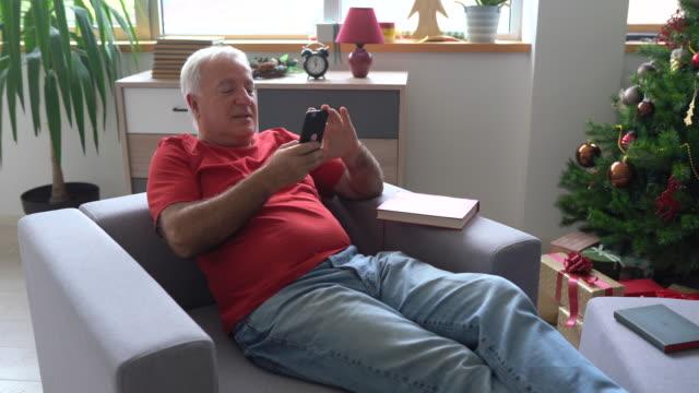 vidéos et rushes de homme aîné appréciant son temps seul à la maison et utilisant le smartphone - seniornaute