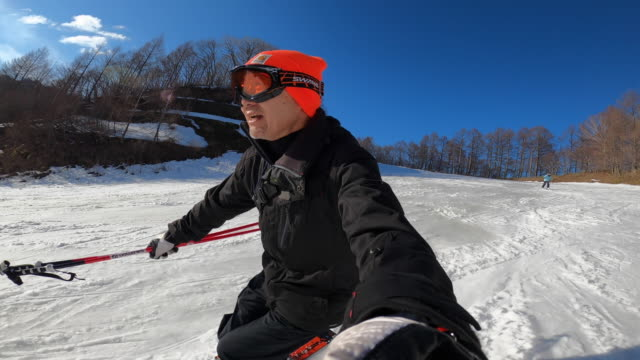 a senior man enjoying skiing with a go-pro and a woman following behind - ski holiday stock videos & royalty-free footage