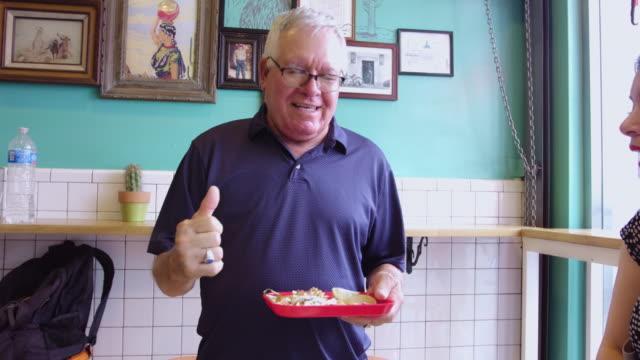 senior man enjoying tacos - mexican restaurant stock videos & royalty-free footage
