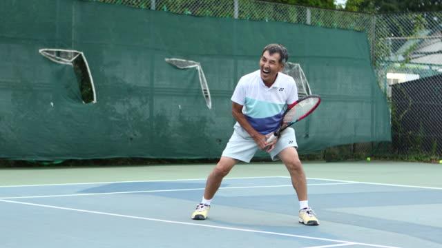 senior man enjoying tennis - オフショット点の映像素材/bロール