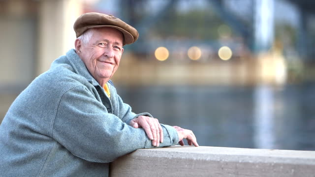 Senior man enjoying waterfront, turns to smile at camera