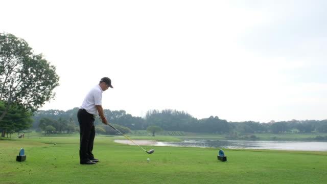 年配の男性がゴルフを楽しんでください。 - ティーショット点の映像素材/bロール