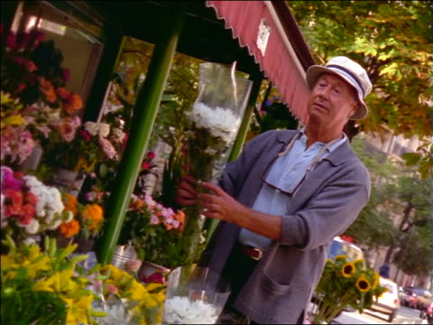 pan senior man examining flowers outside of flower store / france - sonnenhut stock-videos und b-roll-filmmaterial
