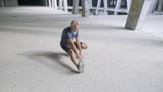 vídeos de stock e filmes b-roll de senior man exercising and stretching before running - esticar