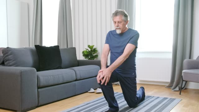senior man exercising in the living room - recreational pursuit stock videos & royalty-free footage