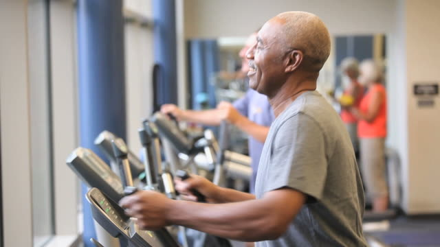 MS PAN TD Senior man exercising on elliptical machine in gym / Richmond, Virginia, USA
