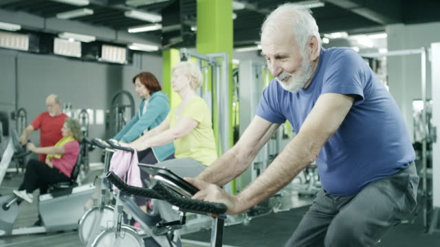 senior man exercising on stationary bike - cardiovascular exercise stock videos & royalty-free footage