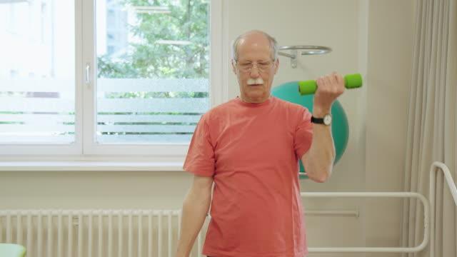 senior man exercising with dumbbells at hospital - rehabilitation center stock videos & royalty-free footage