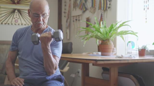 stockvideo's en b-roll-footage met senior man traint met dumbbells - gewichtheffen krachttraining