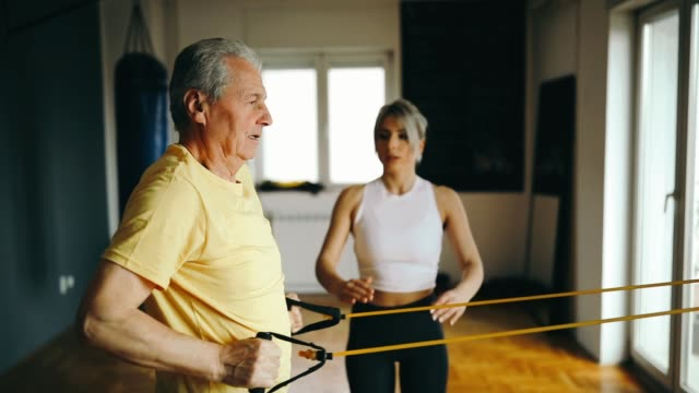 vídeos de stock e filmes b-roll de senior man exercising with the assistance from young woman - personal trainer - artrite