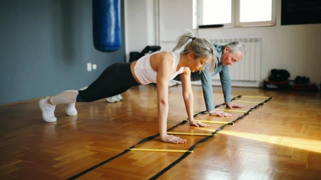 vídeos y material grabado en eventos de stock de senior hombre ejercicio con la ayuda de la mujer joven-entrenador personal - flexiones