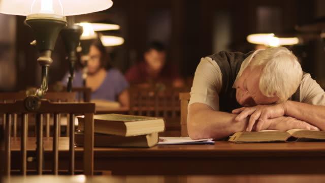 DS Alter Mann beim Einschlafen über Buch in Bibliothek