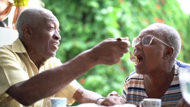 vídeos y material grabado en eventos de stock de el hombre mayor alimentando a su esposa durante el té de la tarde - comer
