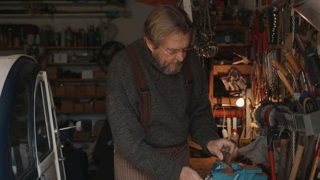 senior man filing piece of wood in garage workshop - workbench stock videos & royalty-free footage