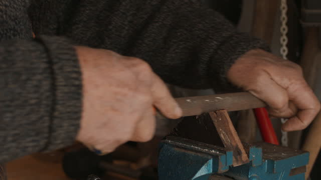 senior man filing piece of wood in workshop - workbench stock videos & royalty-free footage