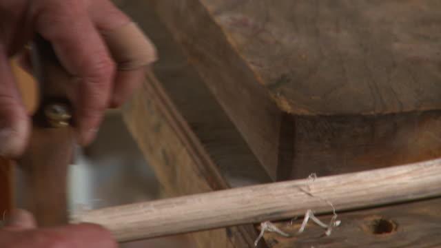 vídeos de stock e filmes b-roll de tu cu senior man filing wooden stick with hand plane in workshop, eastville, virginia, usa - parte de