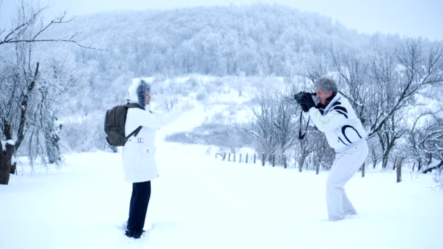 senior man filming his wife in winter nature - frozen stock videos & royalty-free footage