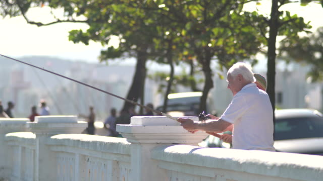 vídeos de stock, filmes e b-roll de senior man fishing at the terrace of city by the sea with trees on the background. - caniço