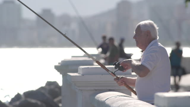 senior man fishing at the terrace of city by the sea with trees on the background. - fishing rod stock videos & royalty-free footage