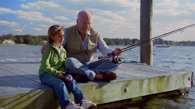 ms, senior man fishing with granddaughter (8-9 years) sitting on pier, usa, pennsylvania - 8 9 years stock videos & royalty-free footage