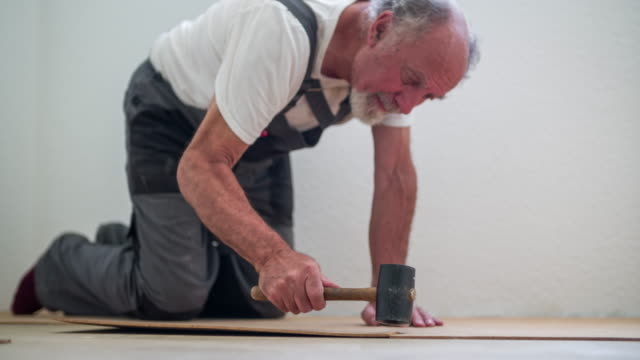 senior man fitting cork flooring in new home - cork material stock videos & royalty-free footage