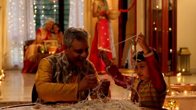 senior man fixing diwali lights with his grandson, delhi, india - capelli corti video stock e b–roll