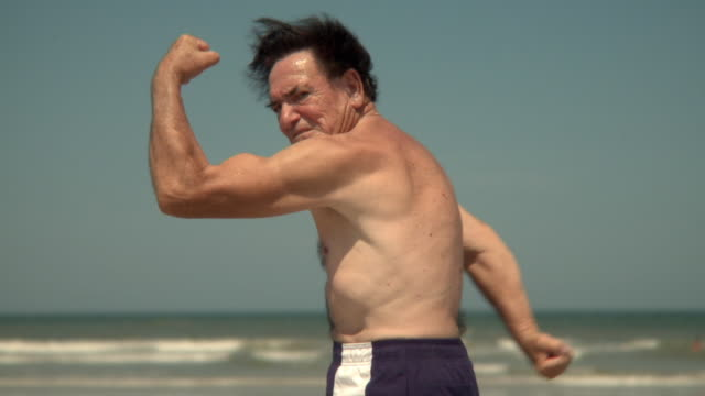 vídeos y material grabado en eventos de stock de slo mo ms senior man flexing muscles on beach, jacksonville, florida, usa - 80 89 años
