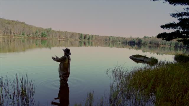 stockvideo's en b-roll-footage met senior man fly fishing in lake - schaduwe