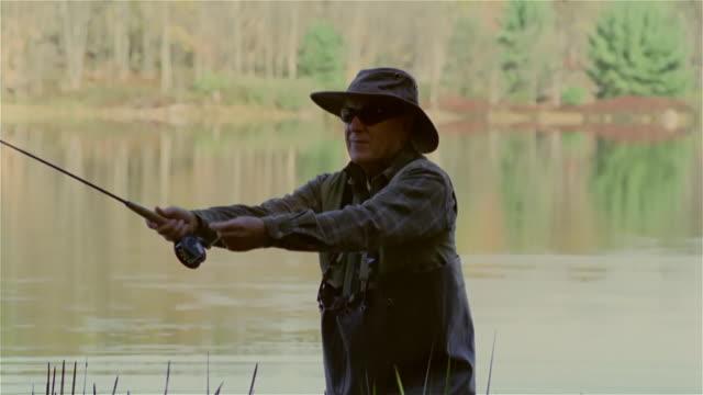 vidéos et rushes de senior man fly fishing in lake - lancer la ligne de canne à pêche