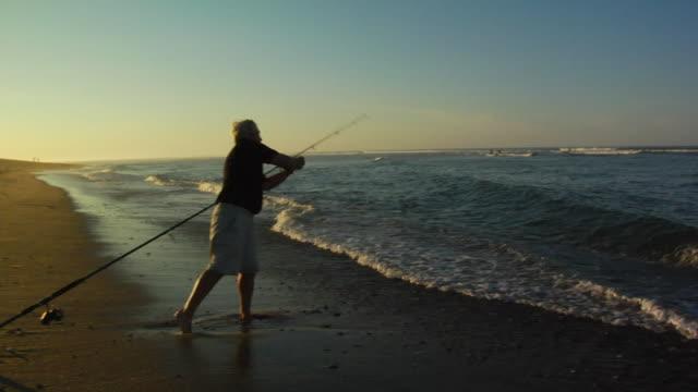 ms, pan, senior man fly fishing on beach, north truro, massachusetts, usa - korta ärmar bildbanksvideor och videomaterial från bakom kulisserna