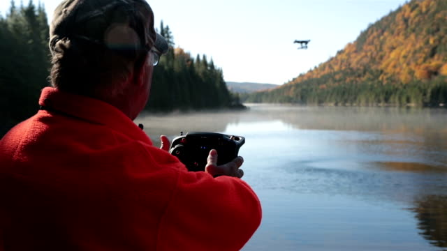 senior man flying a drone, autumn landscape, quebec, canada - radio controlled handset stock videos and b-roll footage