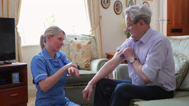 senior man getting a check up at his home - nhs stock videos & royalty-free footage