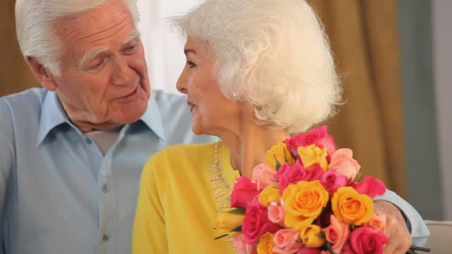 CU PAN TU Senior man giving bouquet of roses to wife / Richmond, Virginia, USA